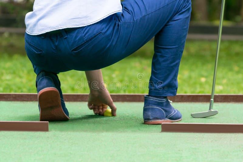 Minigolf-Spieler zieht einen gelben Ball das Loch, hintere Ansicht, Nahaufnahme heraus stockfotos