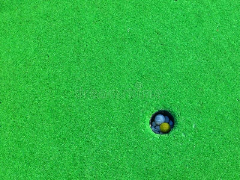 Minigolfbälle in einem Loch lizenzfreie stockfotografie