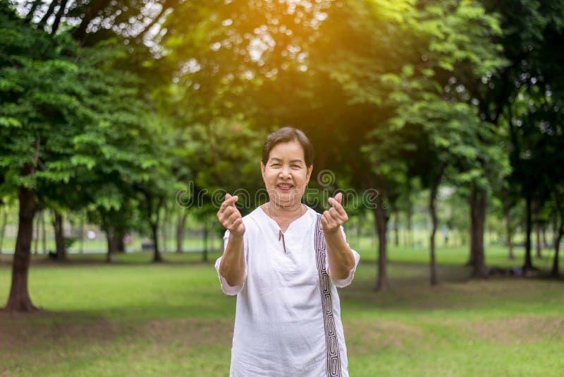 Miniherz zeigende und lächelndes, Positivdenkendes, gesund und lifes Asiatinhände am allgemeinen Park morgens sich entspannen, gl lizenzfreies stockfoto