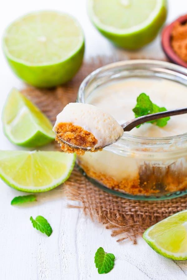 Minikalkkäsekuchen in einem Glastopf auf weißem hölzernem Hintergrund stockfotos