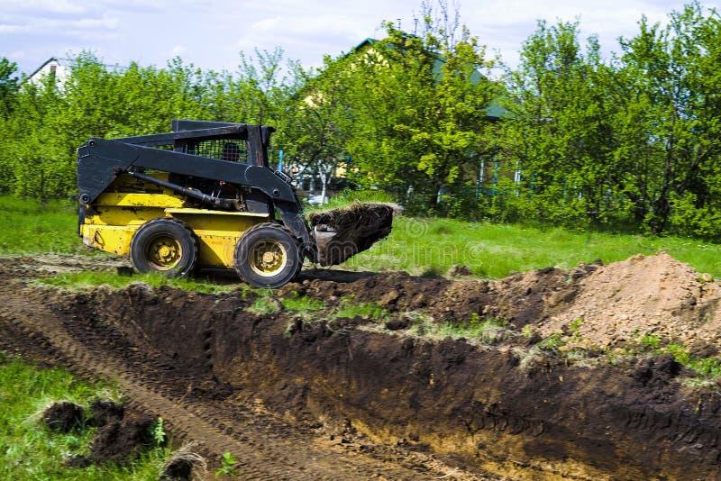 Minilader mit grasartigem Boden im Eimer während der Erdarbeiten in der Landschaft lizenzfreies stockfoto