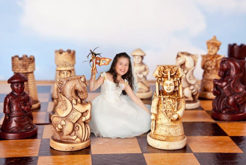 Minimädchen auf Schachbrett lizenzfreie stockfotografie