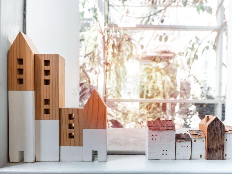Minimaal houten huizen op een witte plank bij vensterglas met zonlicht stock afbeeldingen