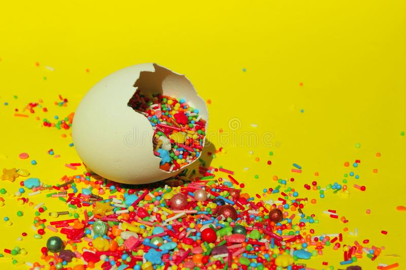 Minimal Art Design. Desserts, Holidays, Birthday Concept. Broken Eggs And Colorful Candies. Multicolored Candy Sweets On Yellow Background. Closeup Of stock images