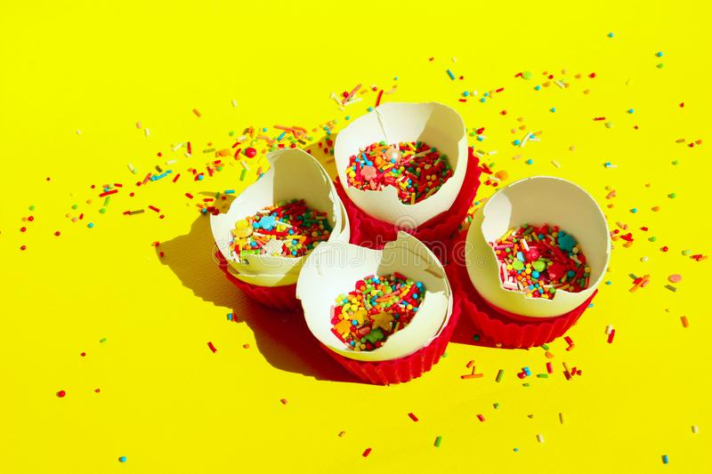 Minimal Art Design. Desserts, Holidays, Birthday Concept. Broken Eggs And Colorful Candies. stock photo