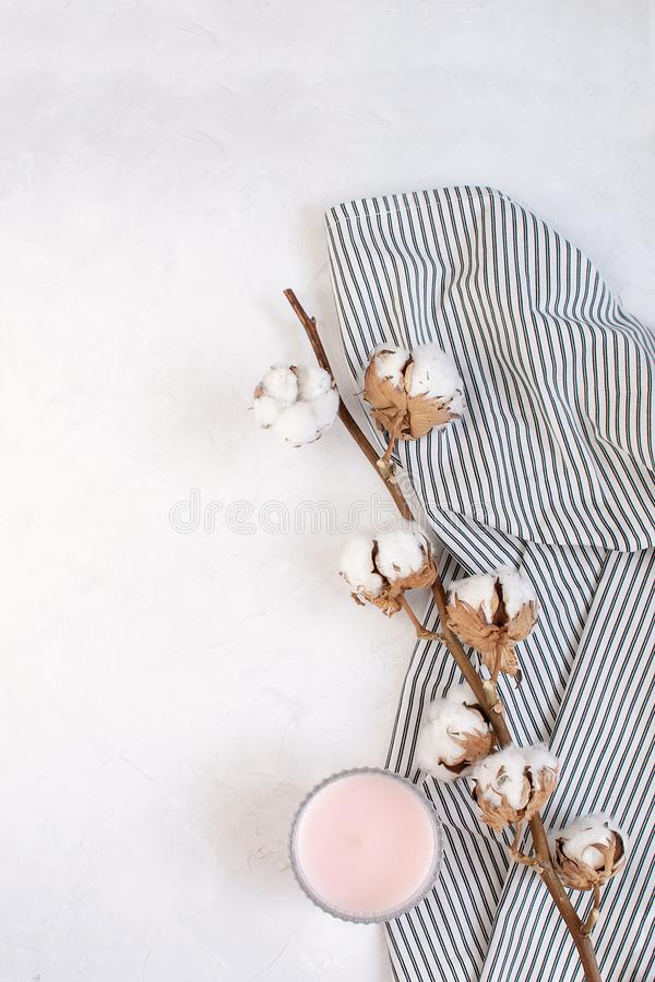 Minimal autumn decor concept - Dried cotton branch, candle. On Crumpled Striped Napkin, white background. Simplicity and softness. Top view, copy space stock images