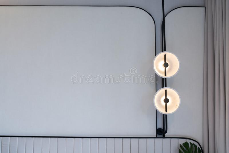 Minimal bedroom corner with circular wall lamp installed on the wall with beige wallcovering in natural light setting scene /. Minimal interior design / modern stock photos