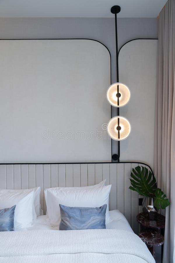 Minimal bedroom corner with circular wall lamp installed on the wall with beige wallcovering in natural light setting scene /. Minimal interior design / modern royalty free stock photo