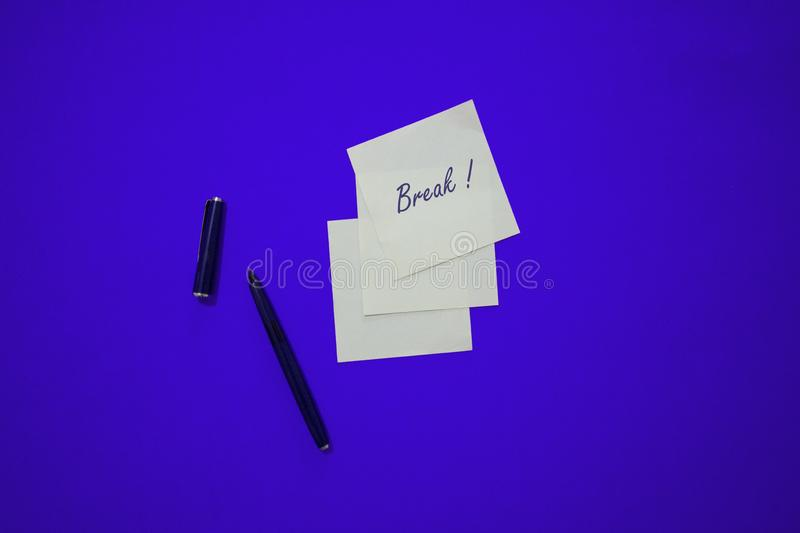 Minimal composition on a colorful pastel background with word `Break` writen on the little paper royalty free stock photography