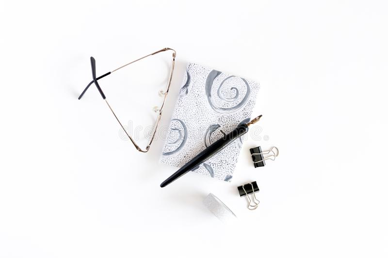 Minimal composition with notepad, glasses, calligraphy pen, black paper clips. On a white background stock images