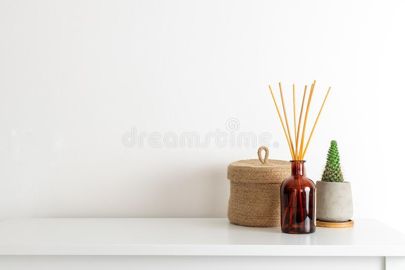 Scandinavian nordic hygge style, home interior - candle, scent aroma diffuser, small straw basket, white shelf. Minimal composition, scandinavian nordic hygge royalty free stock photos