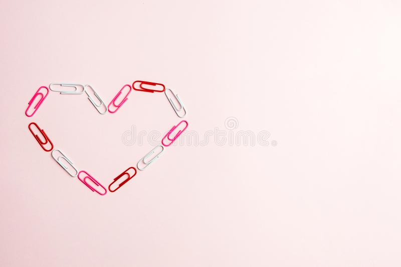 Minimal concept. Heart symbol made of stationery clips on pink background. Flat lay, copy space stock images