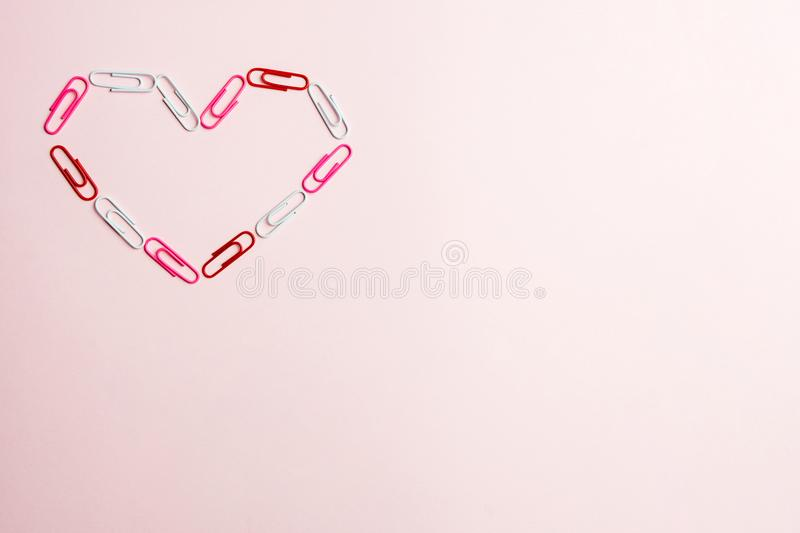 Minimal concept. Heart symbol made of stationery clips on pink background. Flat lay, top view royalty free stock image