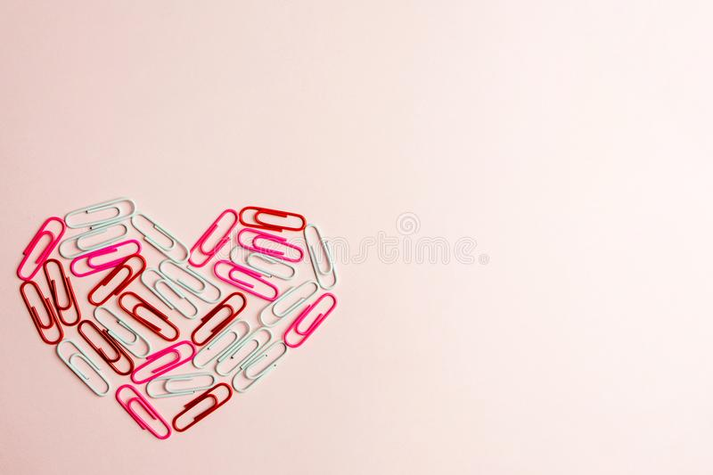 Minimal concept. Heart symbol made of stationery clips on pink background. Flat lay, top view stock photos