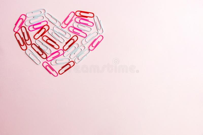 Minimal concept. Heart symbol made of stationery clips on pink background. Flat lay, top view stock photography