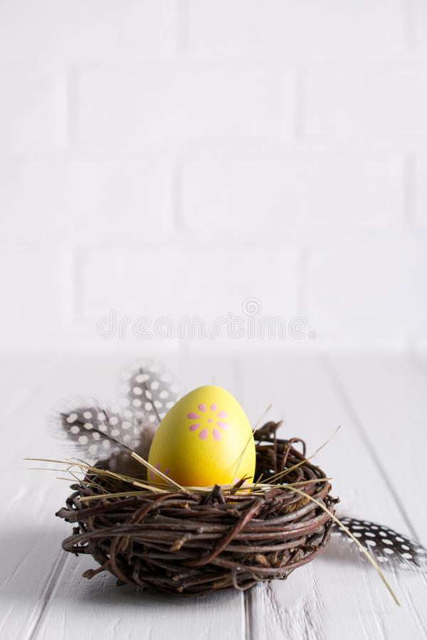 Minimal easter composition. Yellow decorative chicken egg in the nest. Mimosa flowers and feathers. Place for text stock images