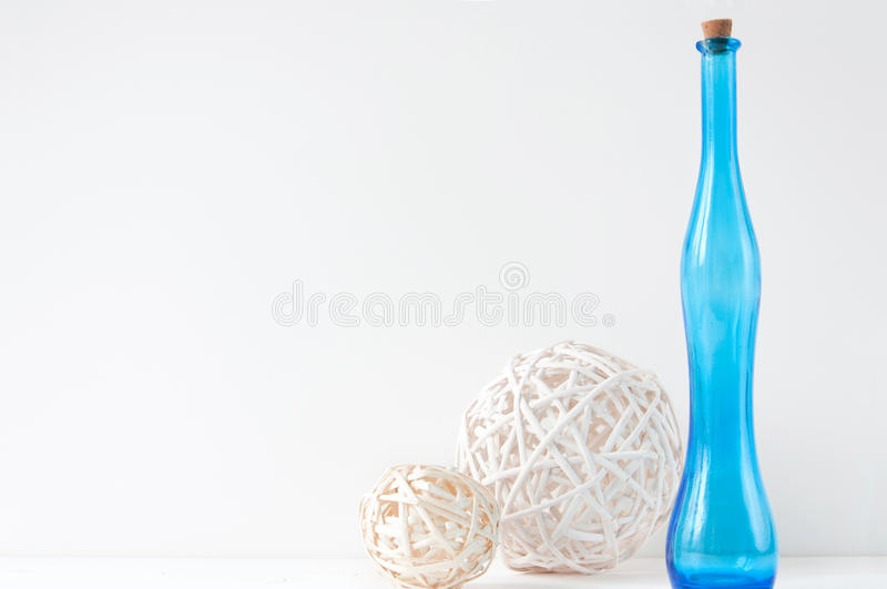 Minimal elegant composition with rattan balls and blue bottle stock photography