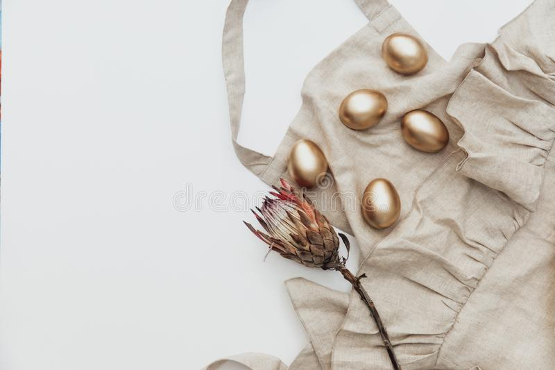 Minimal Flat lay Gold Easter eggs with linen apron and protea flower on white background. stock image