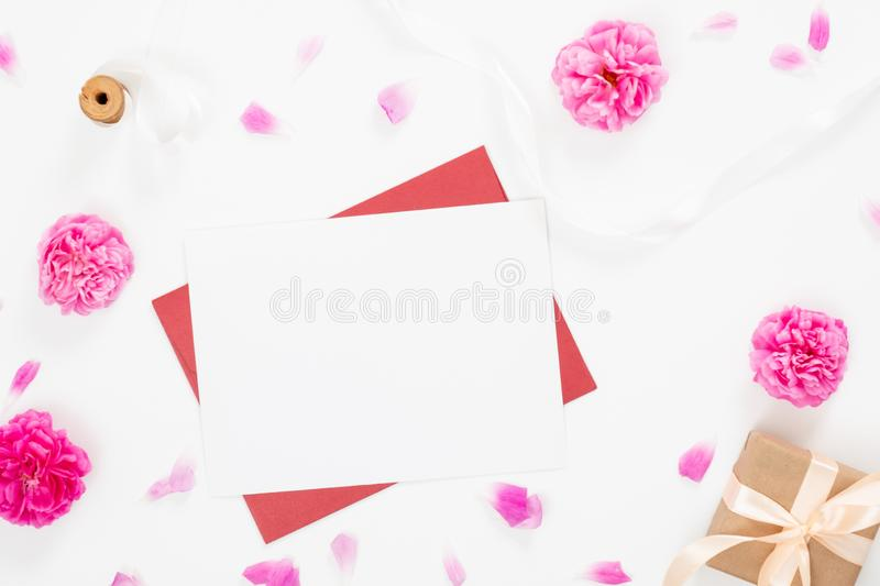 Minimal flat lay style composition with a red envelope, white blank card and pink roses flowers on white background. Top view royalty free stock photography