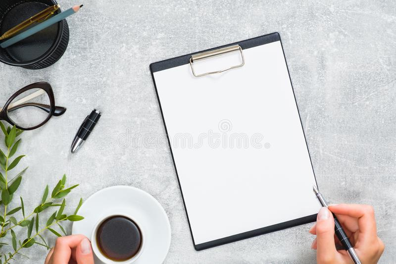 Minimal home office desk with blank copy space mockup clipboard, hands of woman holding coffee cup and pen, green branches on stock photo
