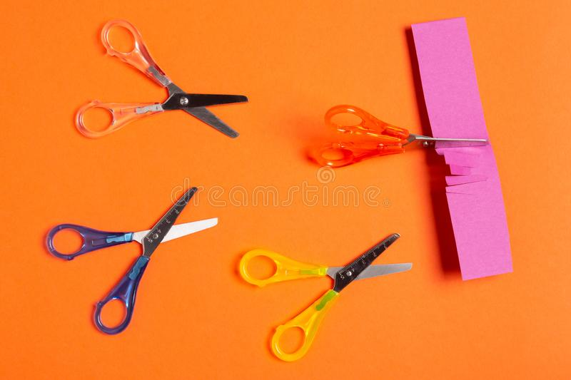 Minimal leadership concept, four colored scissors on an orange background, scissors cut paper, business stock photo