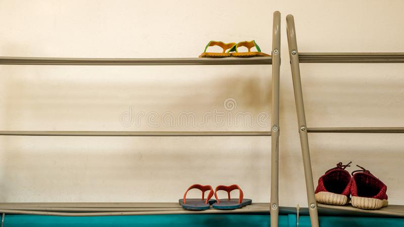 Minimal Metal Shoe Rack with Flip Flops and Red Shoes - Vintage. Minimal Metal Shoe Rack with Two Pairs of Flip Flops and a Pair of Red Shoes. White Wall Texture royalty free stock image