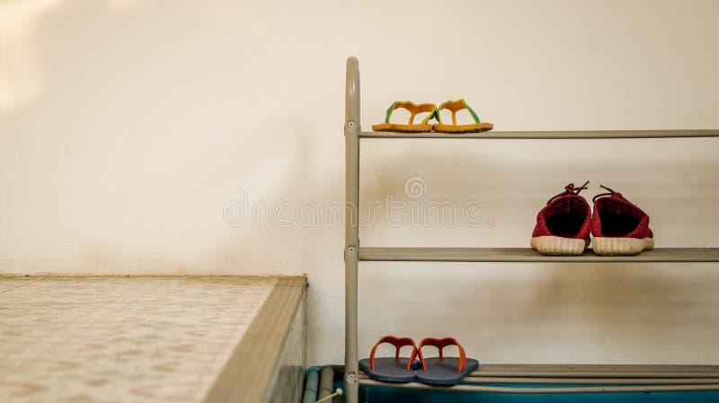 Minimal Metal Shoe Rack with Flip Flops and Red Shoes - Vintage. Minimal Metal Shoe Rack with Two Pairs of Flip Flops and a Pair of Red Shoes. White Wall Texture stock photos