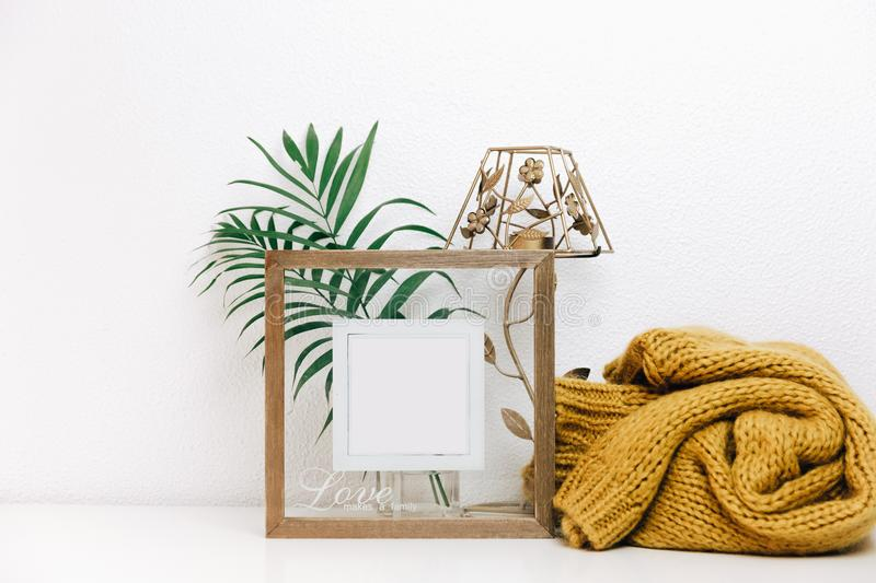 Minimal Mock up wooden frame with green tropical leaves and trendy warm sweater royalty free stock images