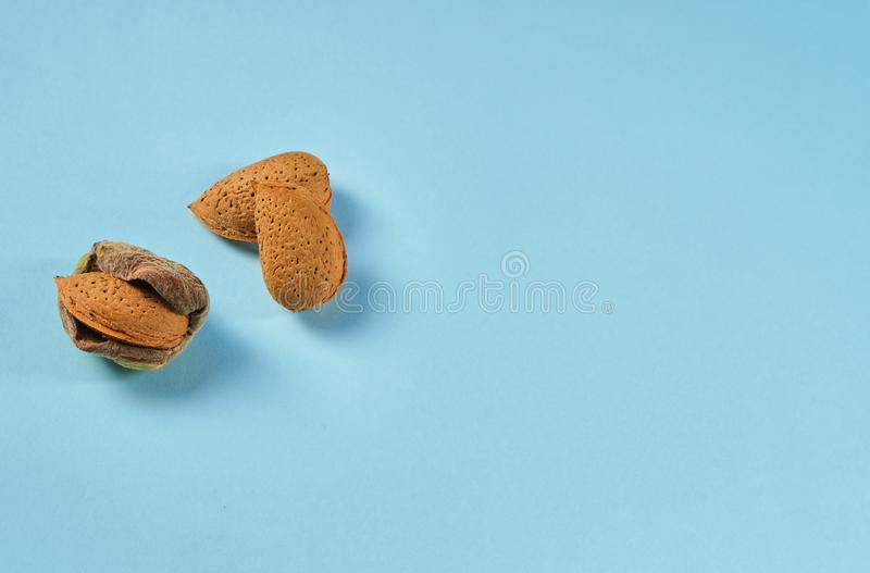 Minimal modern composition with nuts, unshelled Almonds on blue background stock photo