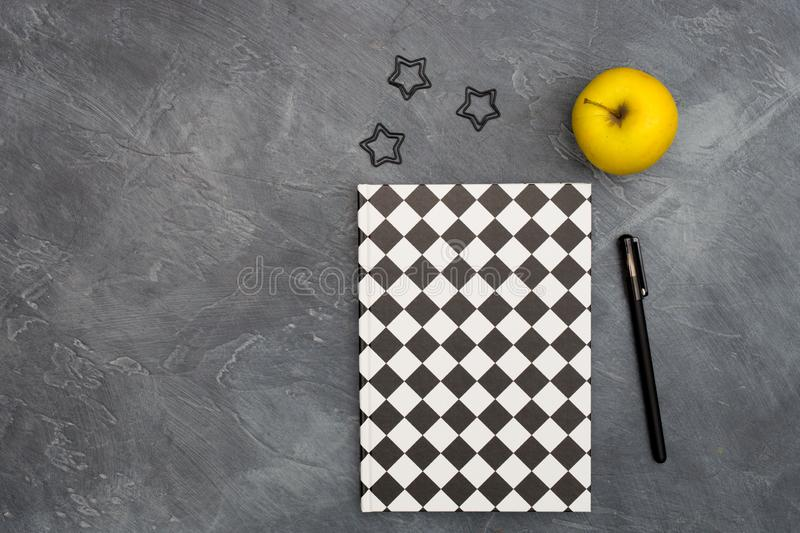 Minimal office concept. Black paper clips, bright yellow apple and pen and closed black-white colored copybook on dark stock photo