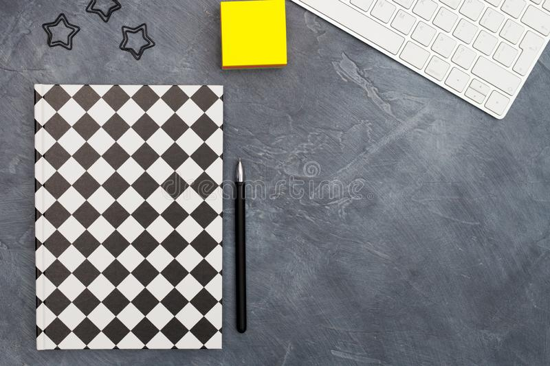 Minimal office concept. Black paper clips, bright yellow sticky note, keyboard and pen and closed black-white colored. Minimal office concept. Black paper clips royalty free stock photos