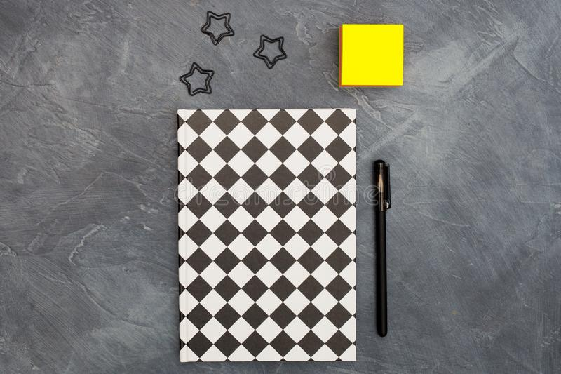 Minimal office concept. Black paper clips, bright yellow sticky note and pen and closed black-white colored copybook on. Dark black abstract background with royalty free stock images
