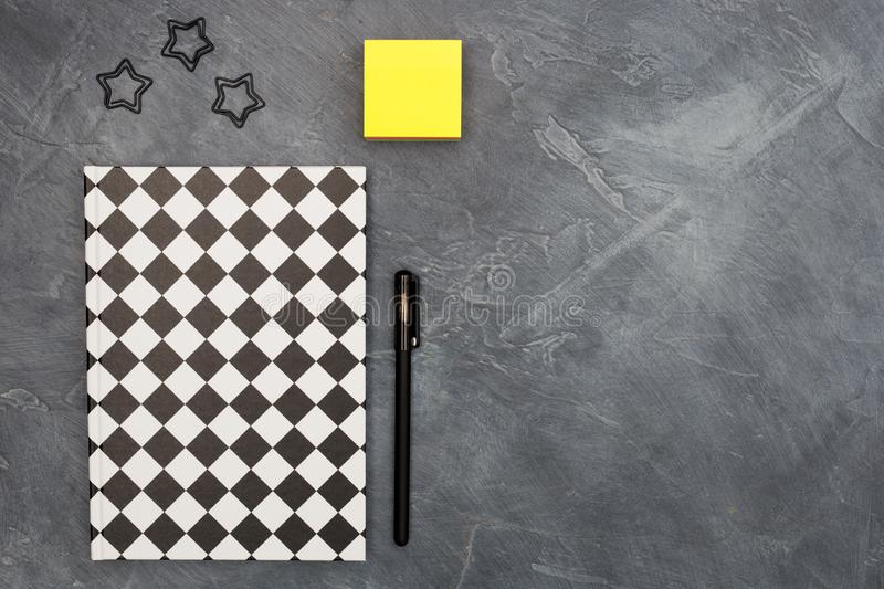 Minimal office concept. Black paper clips, bright yellow sticky note and pen and closed black-white colored copybook on. Dark black abstract background with royalty free stock photography