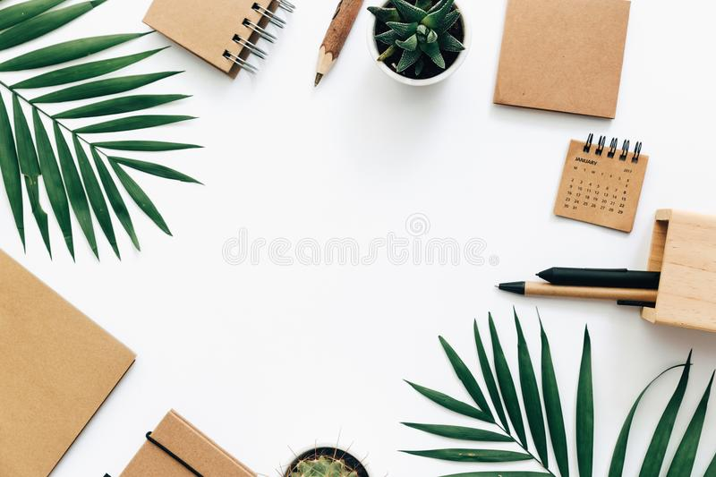 Minimal Office desk table with stationery set, supplies and palm leaves. Top view with copy space, creative flat lay stock images