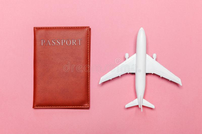Minimal simple flat lay travel adventure trip concept with plane and passport on pink pastel trendy modern background royalty free stock image