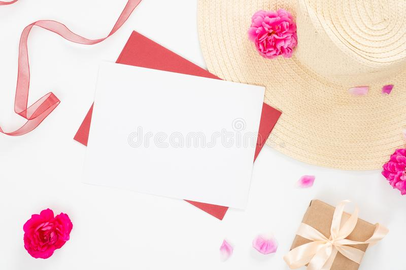 Minimal style composition with blank paper card, craft envelope, beach straw hat, pink rose flowers bud and petal and red ribbon royalty free stock images