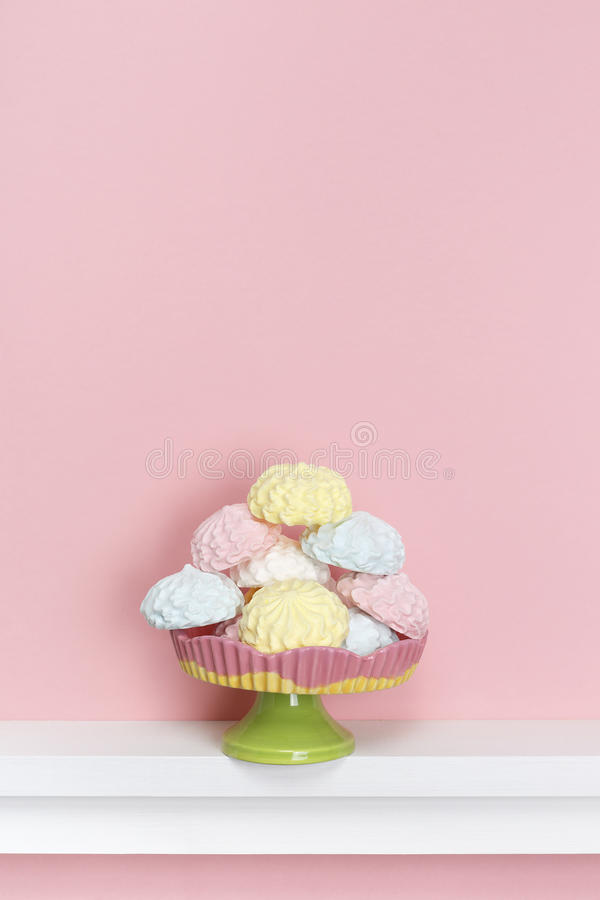Minimal style. Multicolored meringues on a pastel pink background. Sweet desert royalty free stock photography