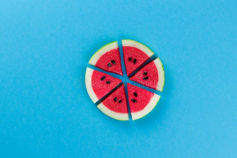 Minimal summer concept made with watermelon fruit slices and black seeds on bright light blue background. Trendy Summer pattern. stock image