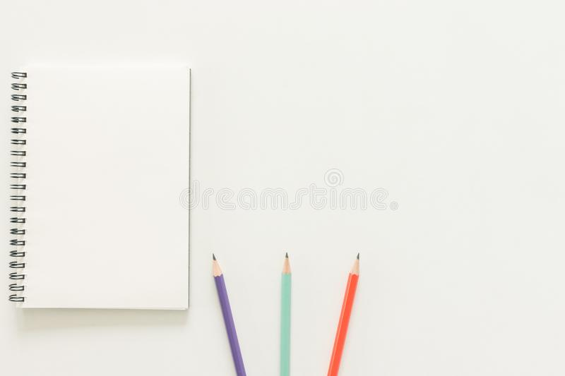Creative flat lay photo of workspace desk with sketchbook and wooden pencil on copy space white background. Minimal work space - Creative flat lay photo of royalty free stock photos