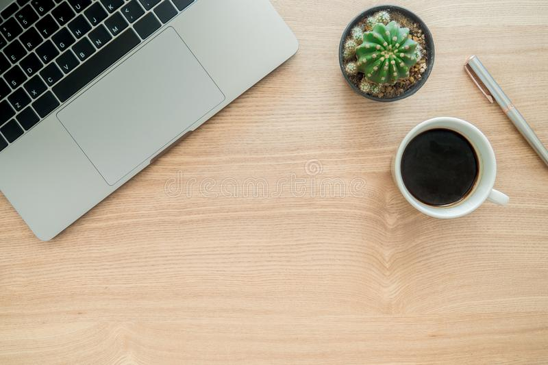 Top view office desk with laptop, plant, coffee cup copy space on wooden background. stock photo