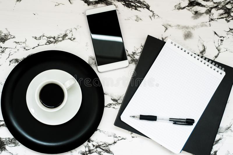 Minimal workspace with coffee cup, notebook and smartphone with copy space on stylish marble background. Top view. Flat lay style royalty free stock photos