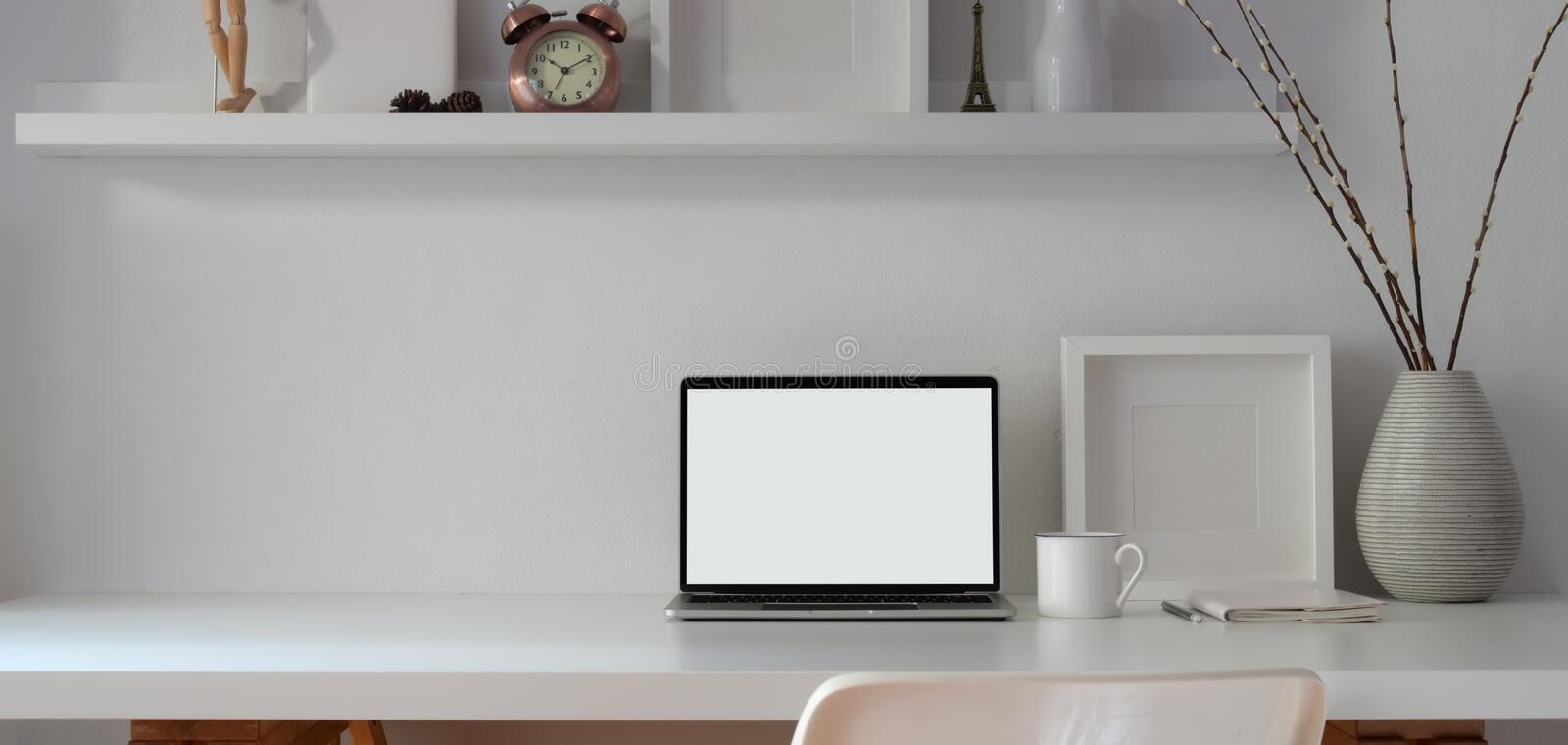 Minimal workspace with open blank screen laptop computer and mock up frame with decorations royalty free stock images