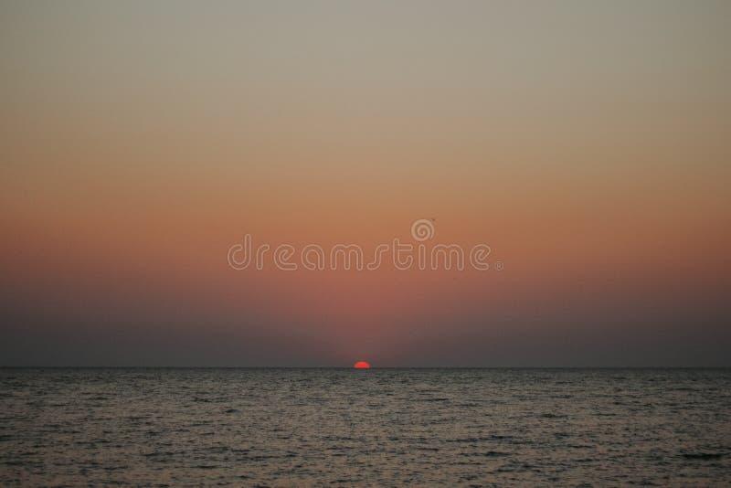 Minimale zon in de het plaatsen zon op het overzees stock afbeeldingen