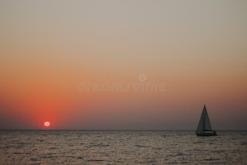 Minimale zon in de het plaatsen zon op het overzees met een zeilboot royalty-vrije stock afbeelding