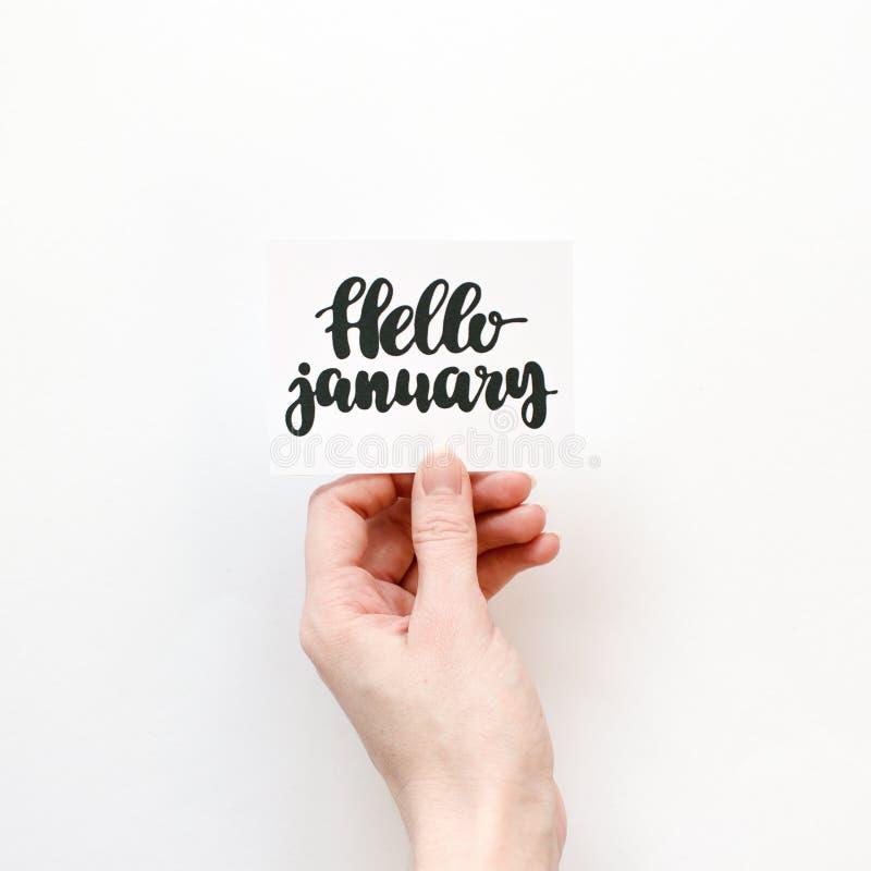 Minimale Zusammensetzung auf einem weißen Hintergrund mit Mädchen ` s Hand, die Karte mit Zitat hallo Januar geschrieben in Kalli lizenzfreie abbildung