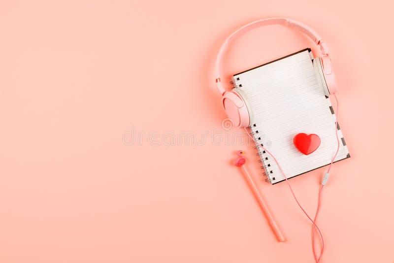 Minimaler Arbeitsplatz mit weißem leerem Notizblock, rosa Kopfhörer, Herz, Bleistift auf korallenrotem Hintergrund Beschneidungsp stockfotografie