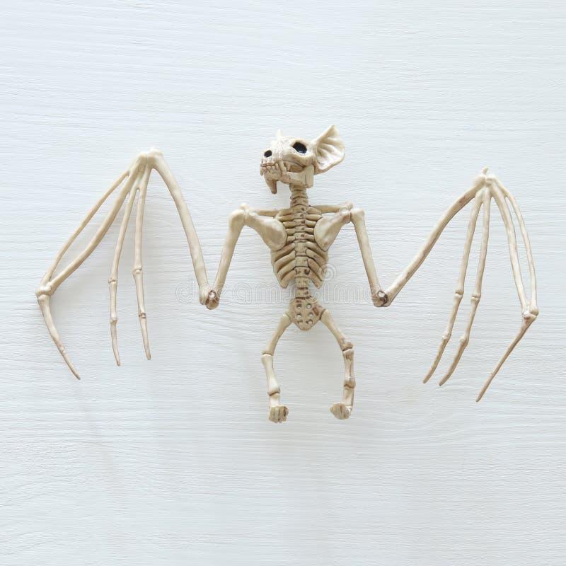 Minimales Draufsichtbild Halloween-Feiertags des Schlägerskeletts über weißem hölzernem Hintergrund lizenzfreies stockbild