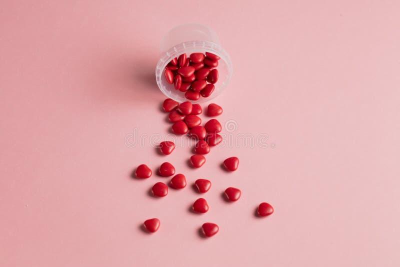 Minimales Konzept rote wenig Herzen mit offener Glasflasche auf rosa Hintergrund lizenzfreie stockfotografie
