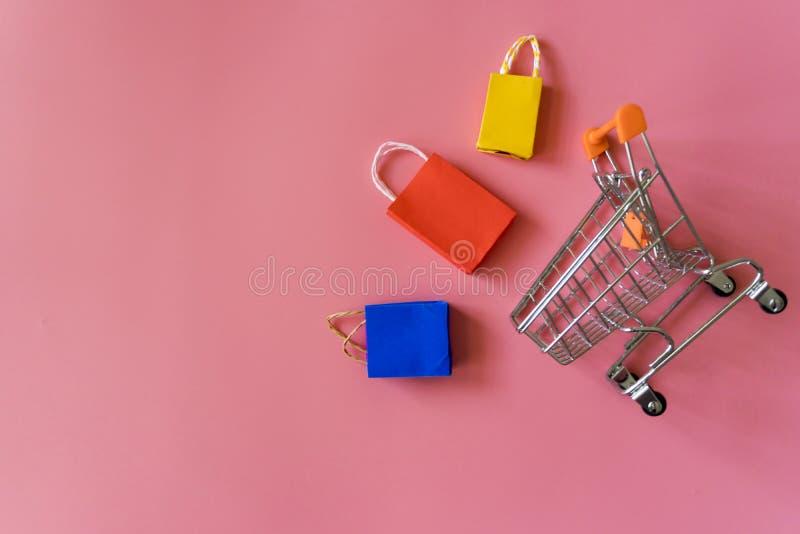Minimales shoping on-line-Konzept, bunte Papiereinkaufstasche und Laufkatze gehen unten vom Schwimmen des rosa Hintergrundes für  lizenzfreies stockfoto