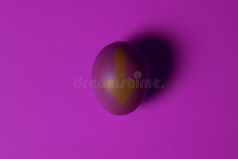 minimalism одно фиолетовое яичко в центре изображения на УЛЬТРАФИОЛЕТОВОЙ предпосылке с нарисованной вниз с стрелки стоковые изображения rf